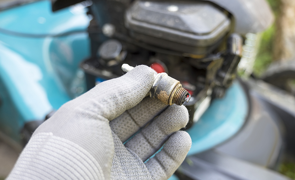 Person holding a lawn mower spark plug.