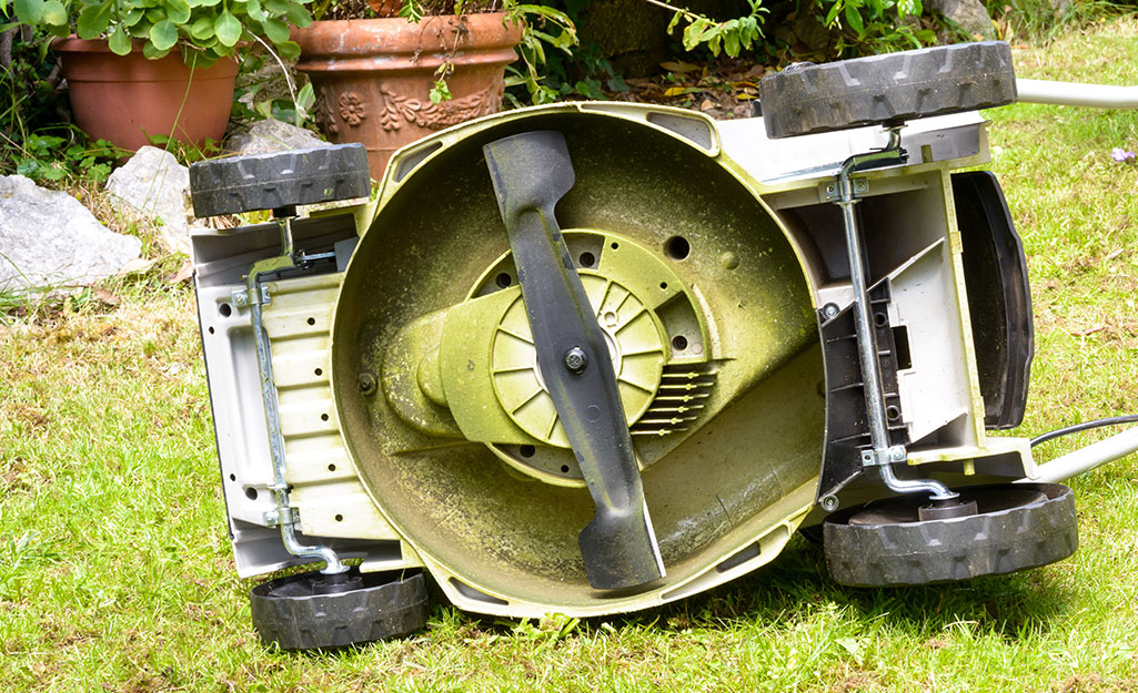 Lawn mower turned on its side to expose the bottom.