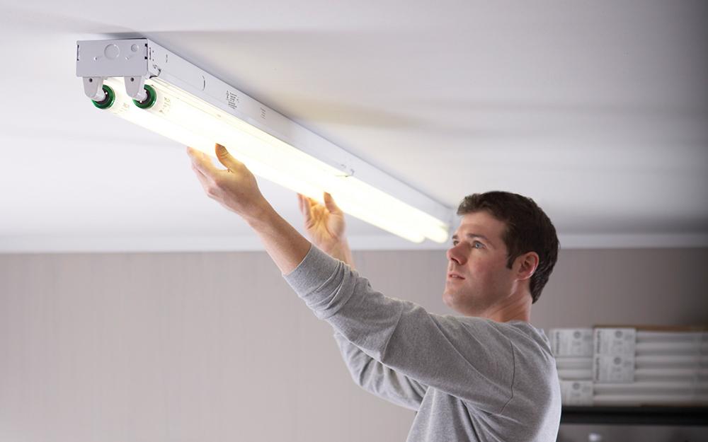 Một người đàn ông đang lắp đặt đèn ống huỳnh quang.