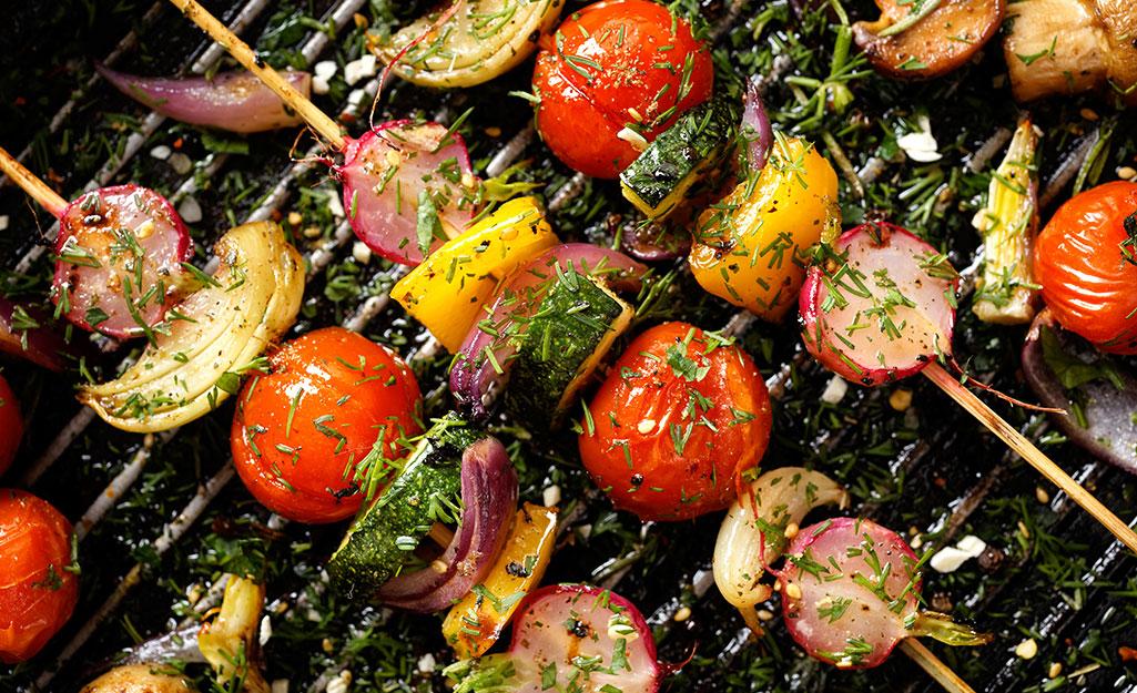 Vegetables cook on a skewer.