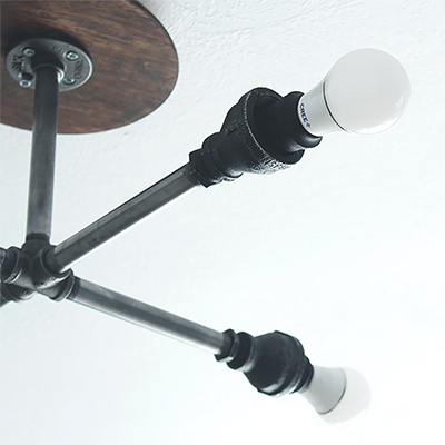 A ceiling with a DIY black pipe light fixture.