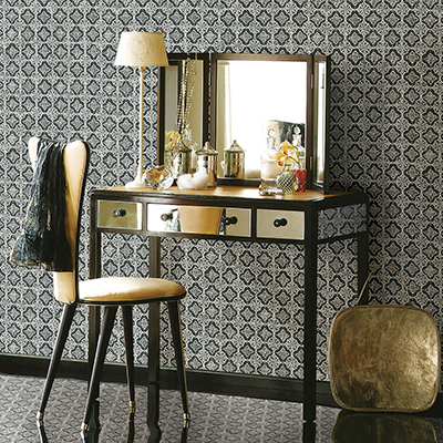 Gold and black makeup vanity sitting in front of wallpapered wall.