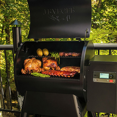 Chicken and ribs sit alongside asparagus, corn and other items in a smoker.