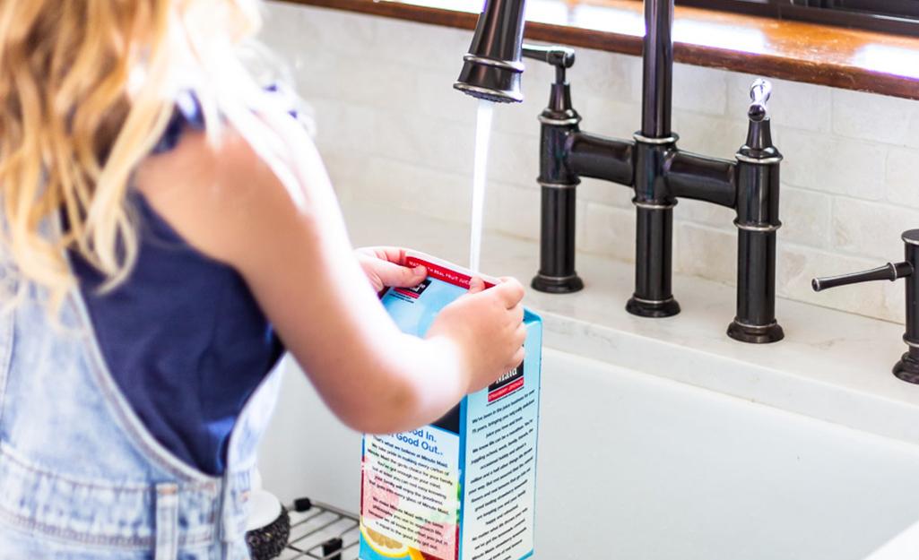 Một cô gái trẻ đang rửa một thùng giấy nửa gallon rỗng.