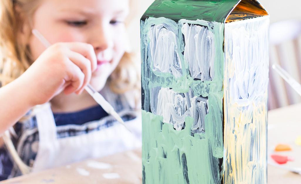 Một cô gái trẻ vẽ một thiết kế trên thùng carton.