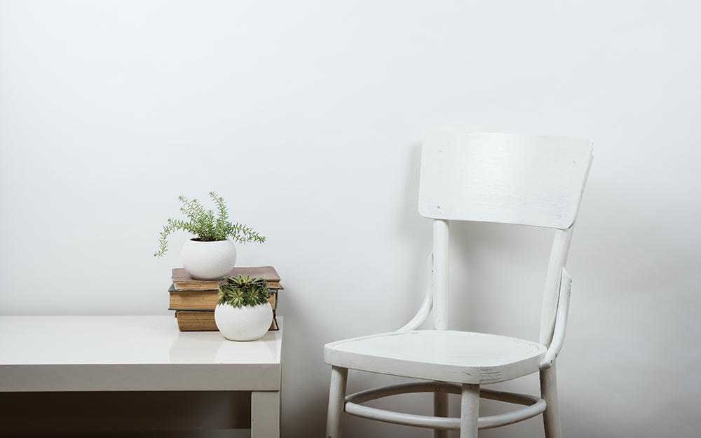 Một chiếc ghế màu trắng bên cạnh một chiếc bàn màu trắng có trồng cây trên đó.
