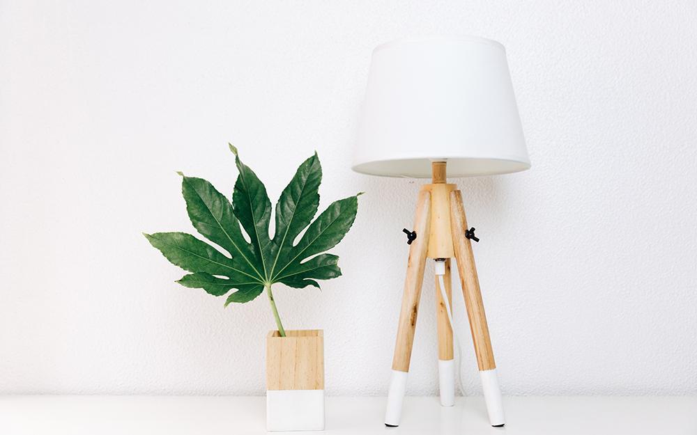 Một chiếc đèn và bình gỗ màu trắng và tự nhiên bên cạnh bức tường trắng.