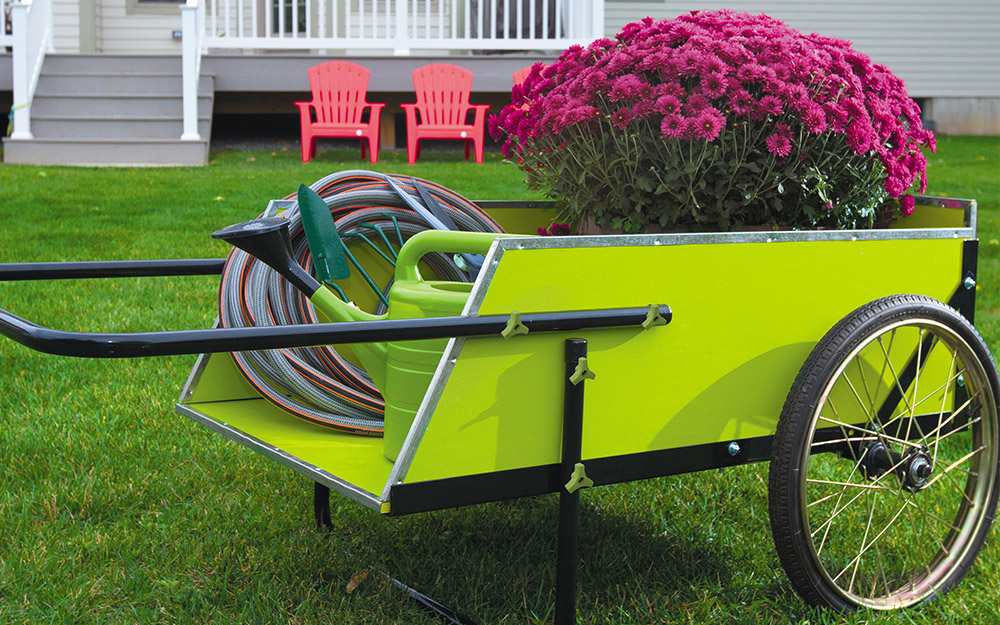 A garden cart with flowers and a watering can and hose.