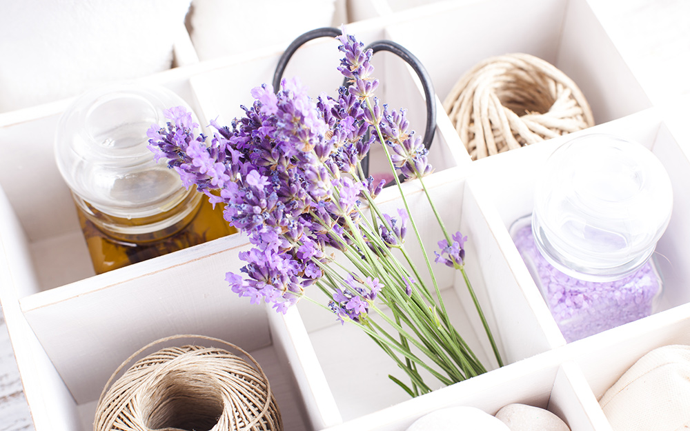 A tote caddy filled with sprigs of lavender and assorted beauty products..