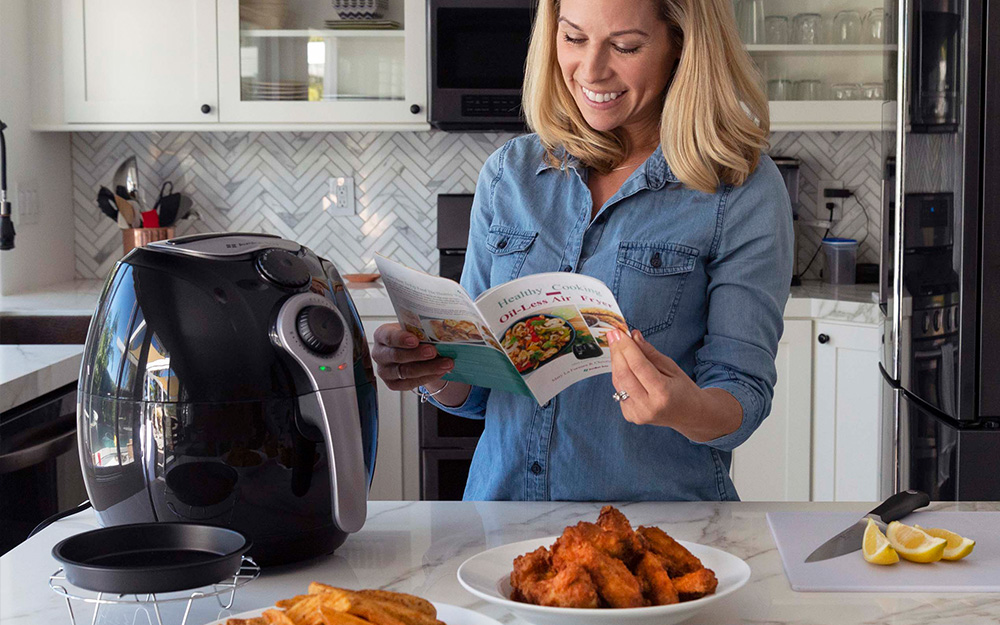 Woman reading a pamphlet beside an air fryer on a countertop.