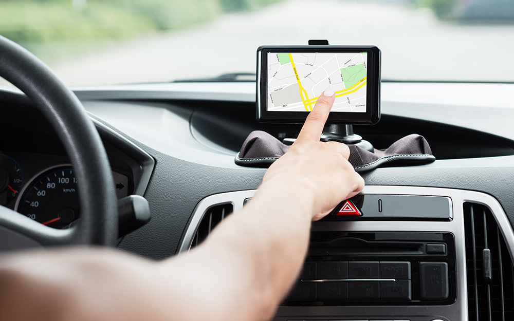A person in a car tapping a Mother's Day gift of a GPS navigation device.
