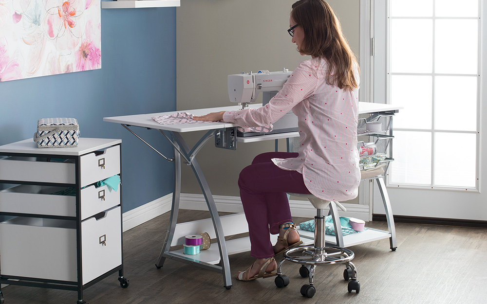 Woman using a sewing machine with storage drawer unit nearby.