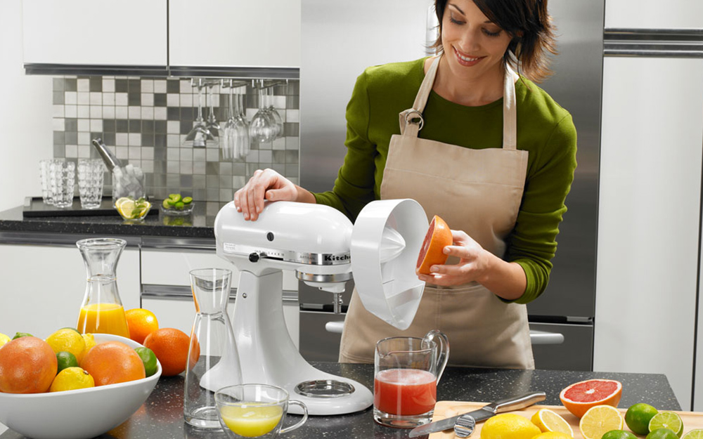 Woman using a kitchen mixer with attachment to juice fruits.