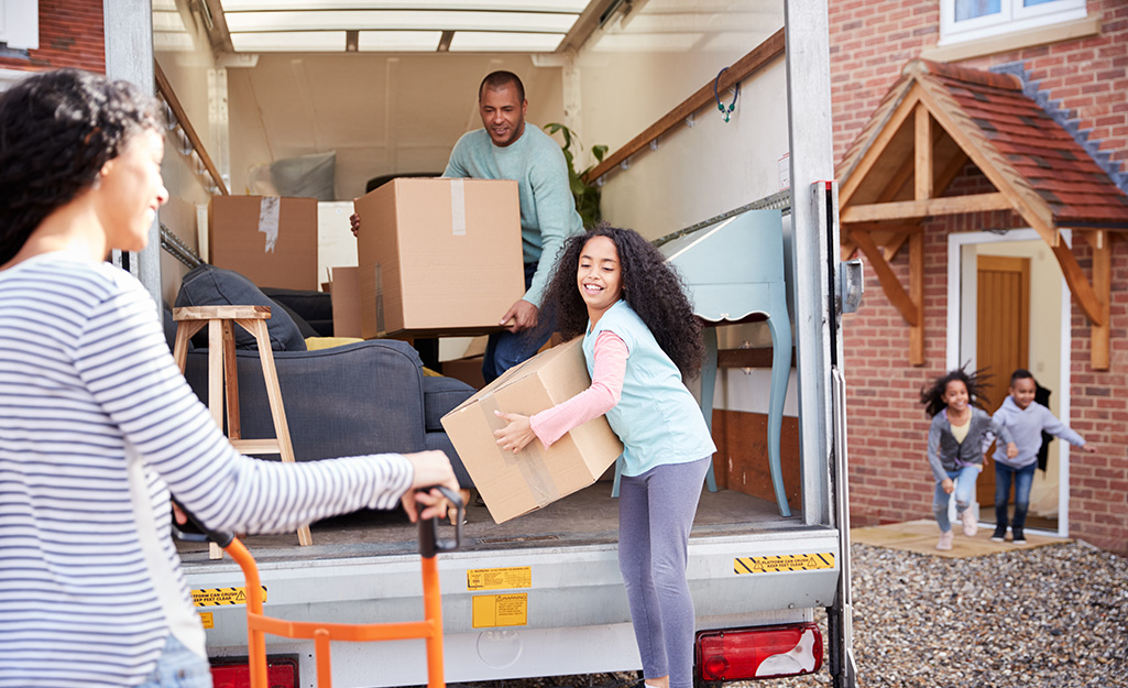A group of people unloading a moving truck in front of a house.