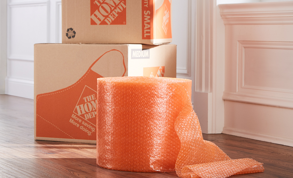 Orange bubble wrap and moving boxes sitting next to a door.