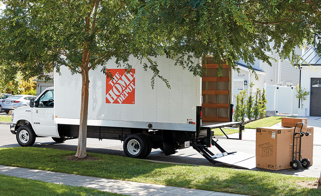 A Home Depot moving truck parked on the street in a neighborhood.