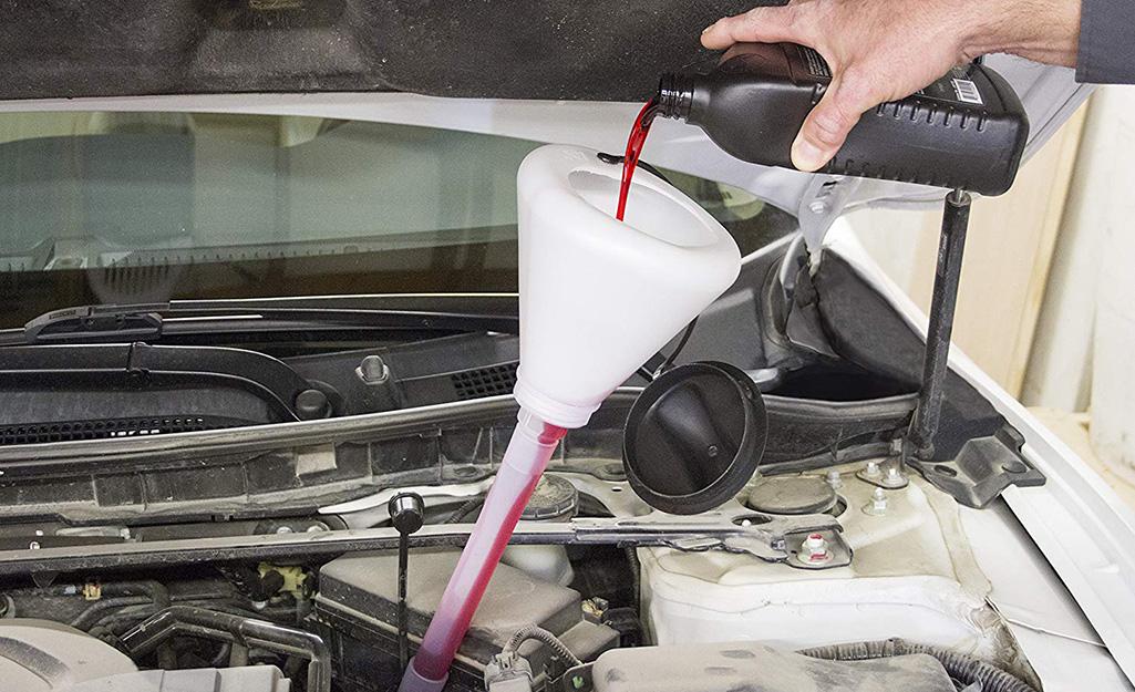 Một bàn tay đổ dầu vào phễu dưới mui xe ô tô