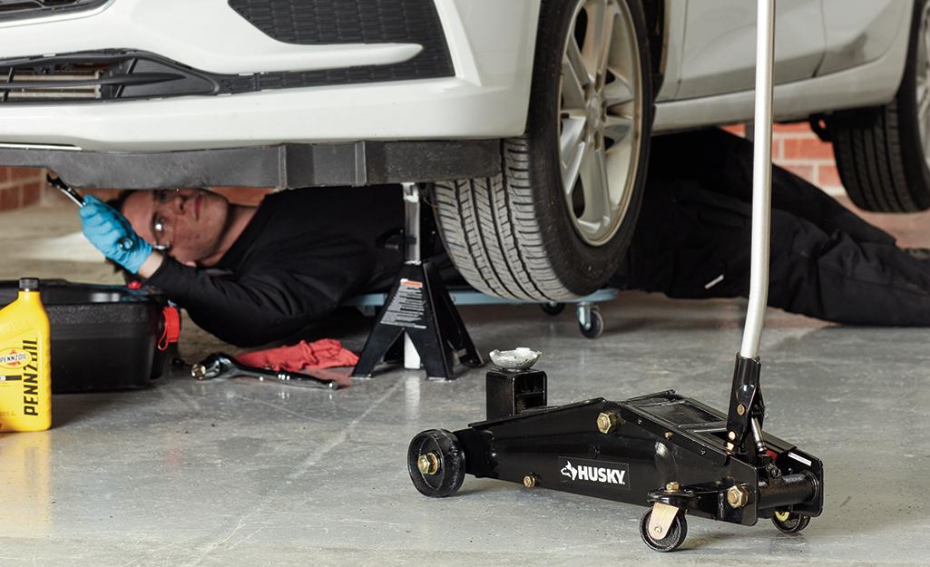 Một người đàn ông nằm trên bánh xe dolly dưới một chiếc xe hơi