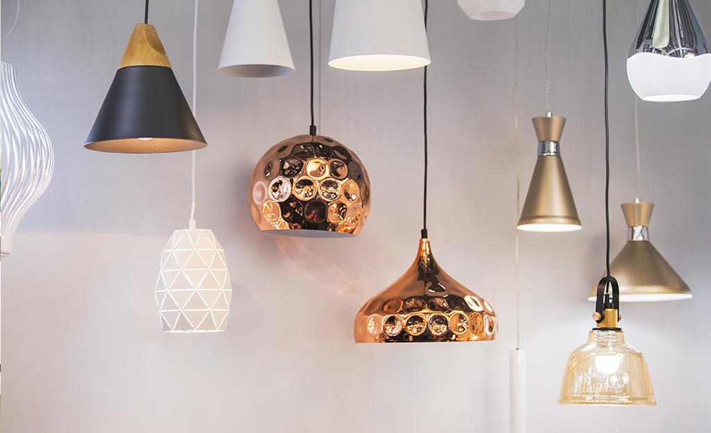 Một số đèn mặt dây chuyền bằng kim loại đồng, trắng và bạc treo trên tường trắng.