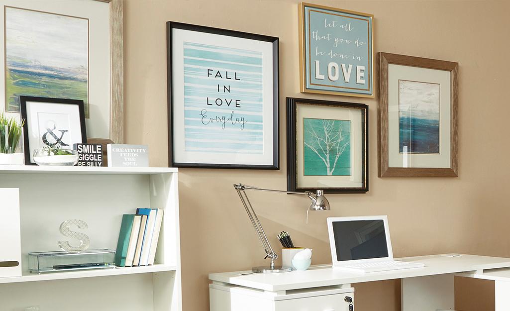 Nghệ thuật treo tường phía trên bàn làm việc nhỏ nhắn trong văn phòng tại nhà.
