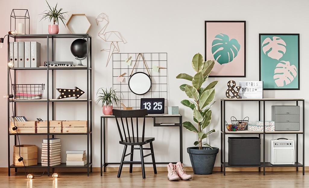 Giá sách kim loại đen dựa vào tường với nghệ thuật treo tường màu hồng và xanh