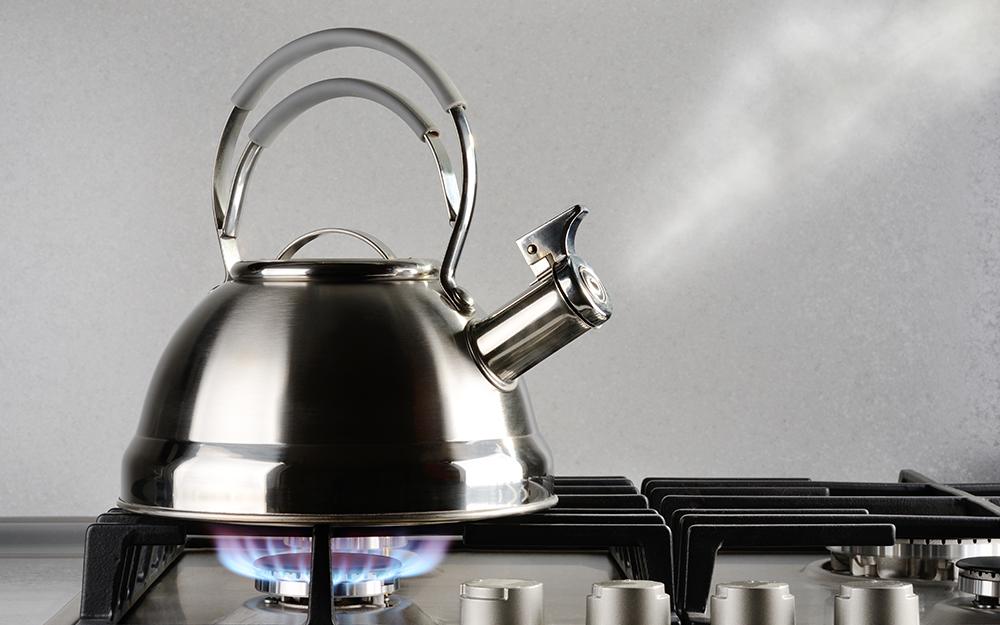 Tea pot boiling on a stove.