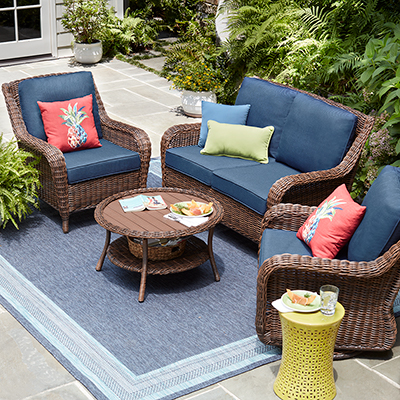 An outdoor living space with a rug, sofa and chairs and accent tables.