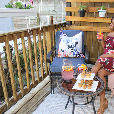 A woman sitting on a small balcony with wall planters.