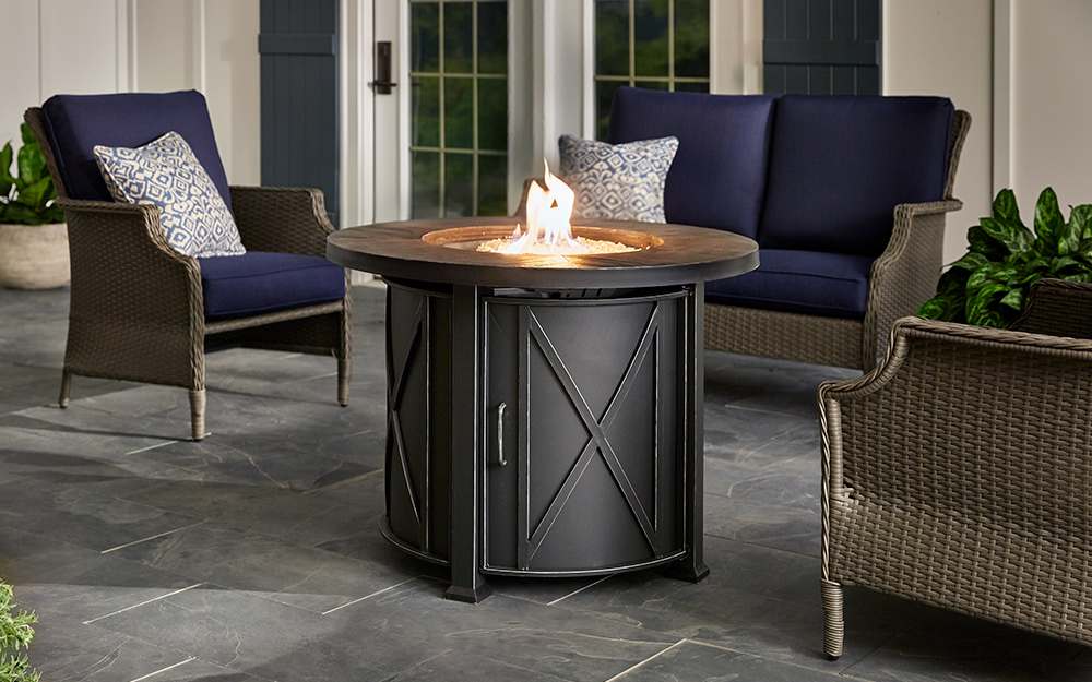High-back patio furniture next to a gas fire pit.