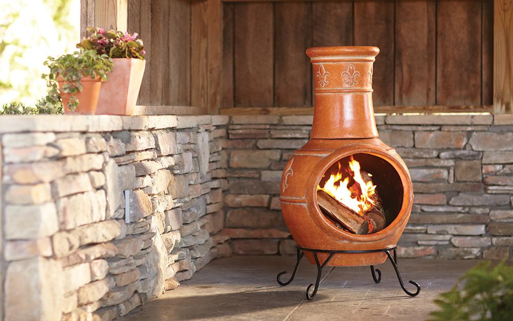Terracotta chimenea fire pit in the corner of a stone courtyard.