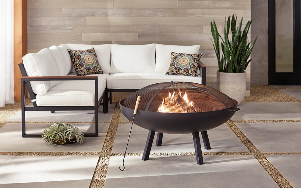 Circular wood-burning metal fire pit beside outdoor furniture.