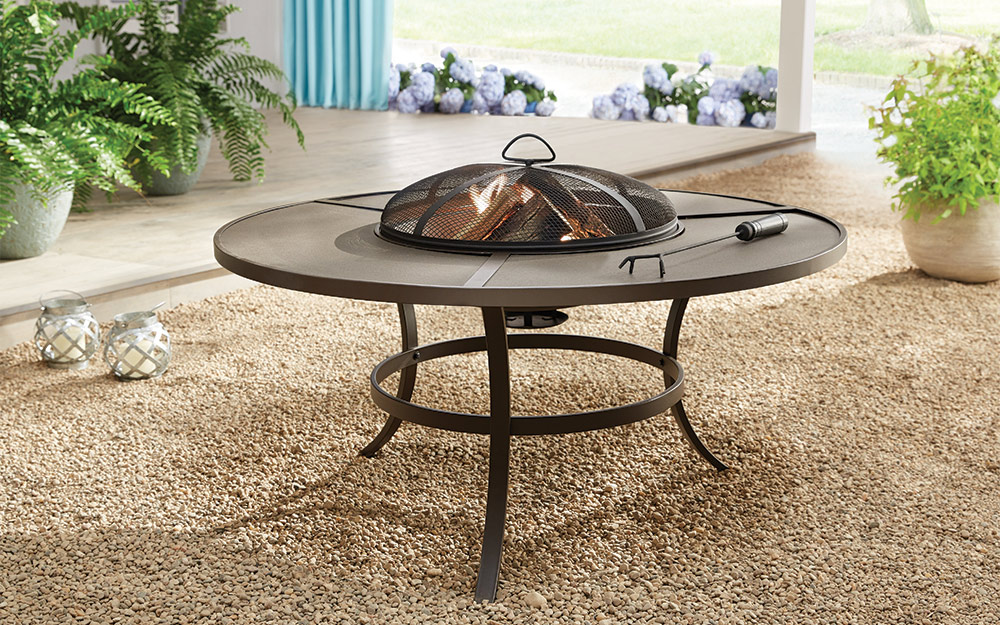 Round fire pit sitting on river pebbles.