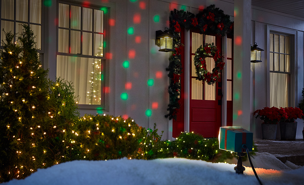 A holiday light projector shines colored circles of light on the front of a home.