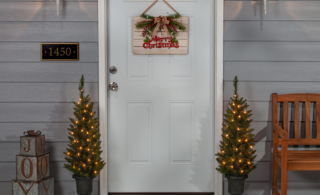 Two small porch Christmas trees flank a home's front door.