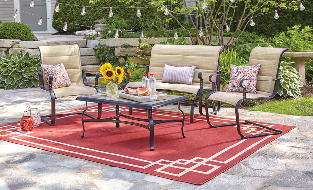 một tấm thảm ngoài trời trên sân sau với chỗ ngồi ngoài trời