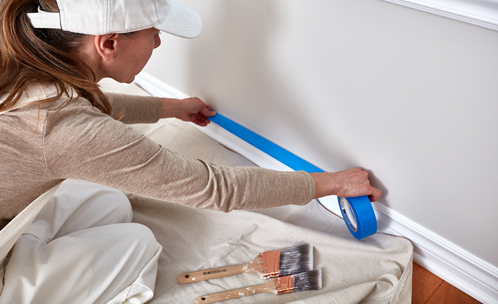 A woman applying painter's tape to wall moulding.