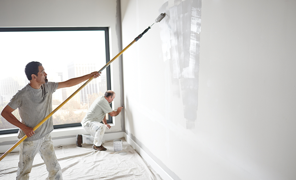 Two men painting a room that is brightly lit with natural light.