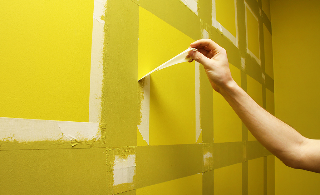 A person removing tape from a recently painted wall.