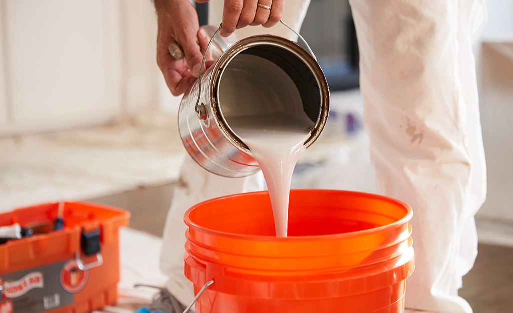 Someone pouring a can of paint into an orange bucket.
