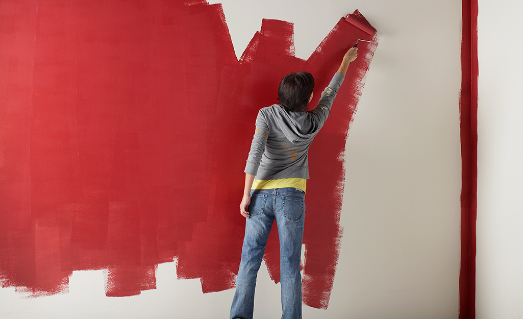 Woman painting a room from the top down.