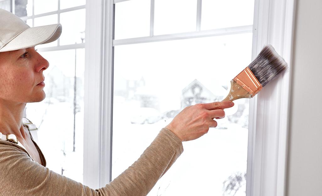 Woman painting trim white.