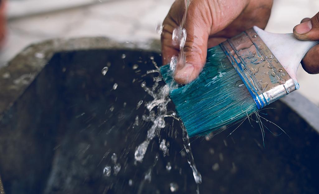 Hand washing green paint brush with water.