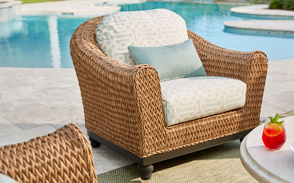 Wicker patio chair beside a swimming pool.