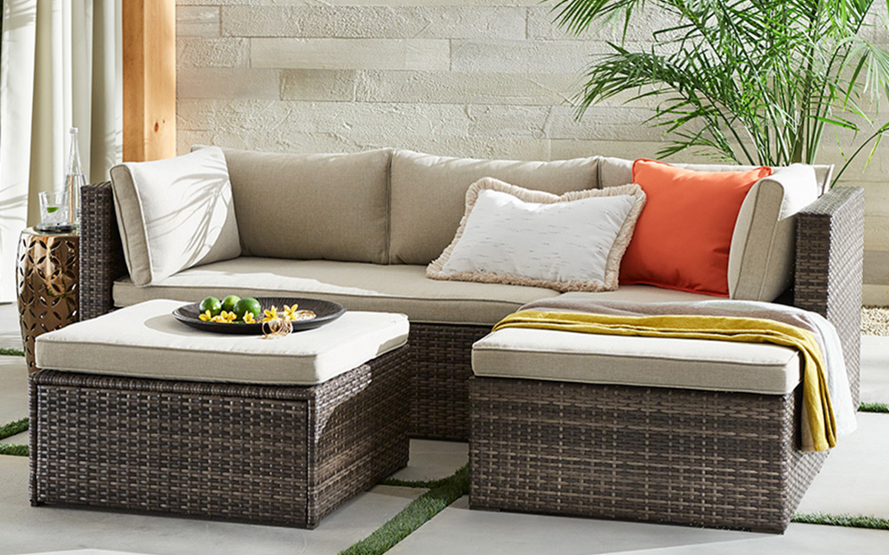 Outdoor sofa and two cushion-topped ottomans on a patio.
