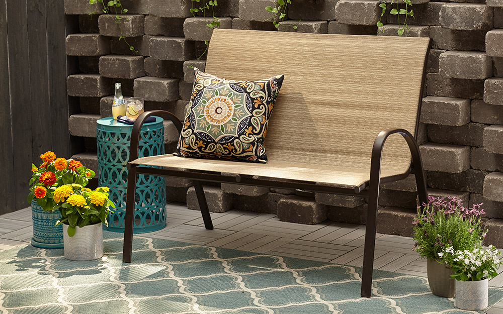 Metal and wicker bench on patio.