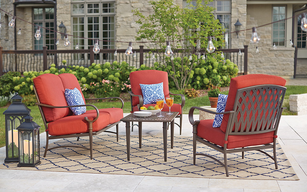 Matching metal chairs with colorful cushions and pillows on a patio.