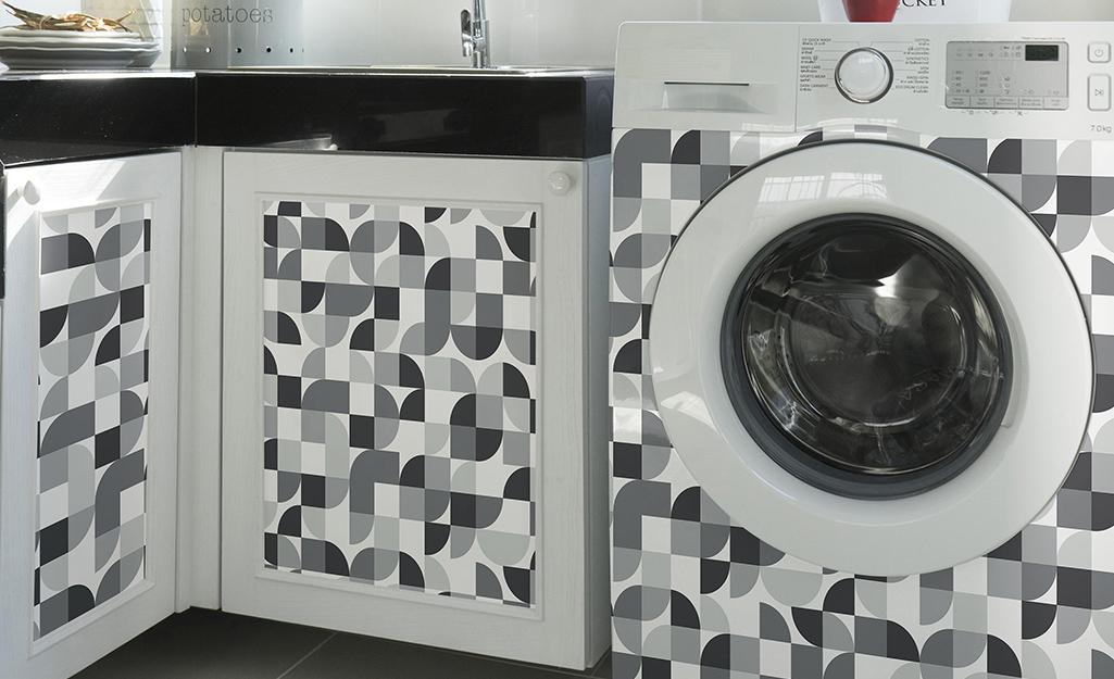 Hình học bóc và dán giấy dán tường trang trí mặt trước của máy giặt và cửa tủ gần đó.