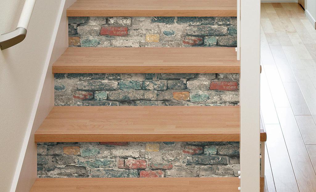 Giấy dán tường giả gạch và dán trang trí mặt trước của bậc cầu thang bằng gỗ.
