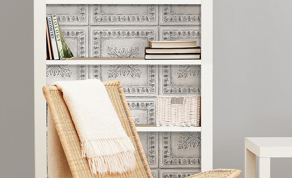 Nội thất phía sau của giá sách màu trắng được trang trí bằng giấy dán tường kiểu cổ điển.
