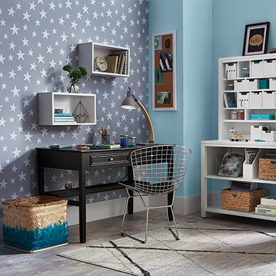 A home office with a star-patterned peel and stick wallpaper accent wall.